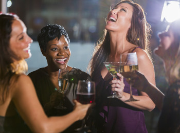 A group of four multi-ethnic women having fun together at a restaurant bar, drinking, talking and laughing.  It is ladies night.  The Asian woman wearing purple is holding a martini as she laughs, and her African American friend has a glass of champagne.  The others are drinking wine.